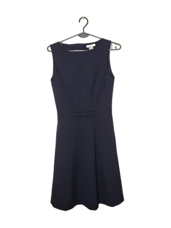 Granatowa sukienka z kokardką z przodu. Zapinana na zamek i guziczek z tyłu.