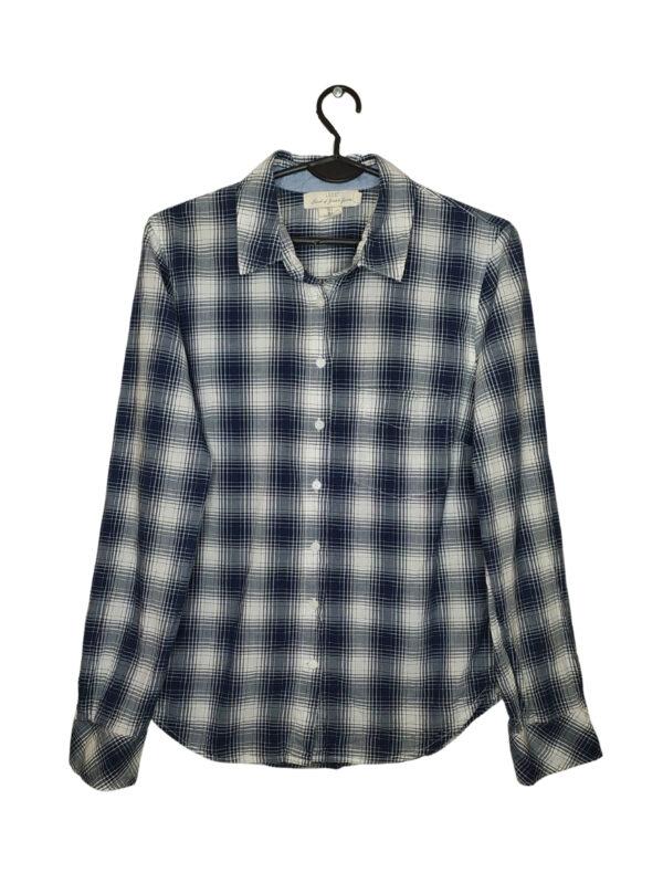 Biała koszula w niebieską kratę. Posiada kieszonkę z przodu. Przy metce zapasowy guzik.