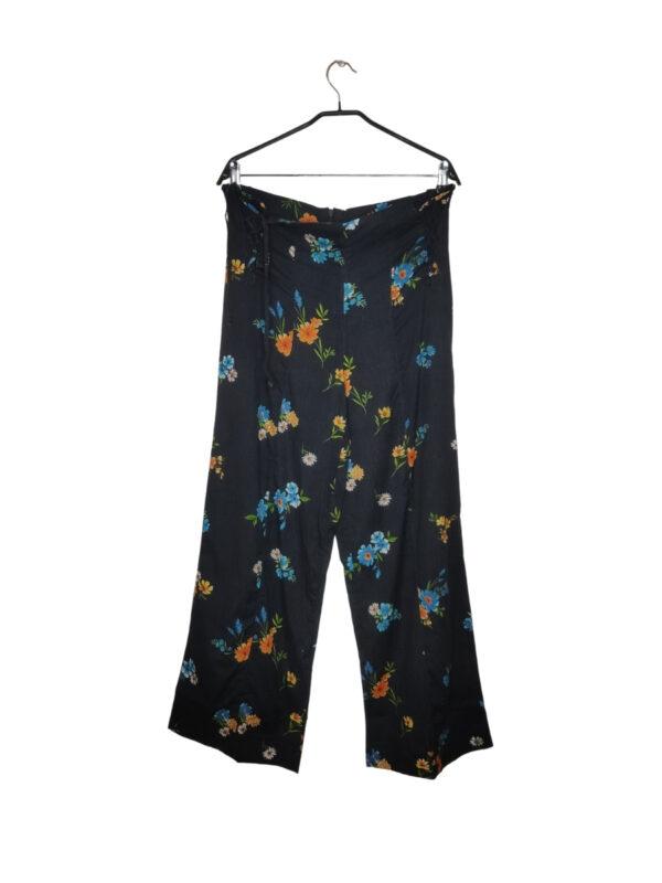Czarne szerokie spodnie w kolorowe kwiaty. Wiązane na biodrach. Zapinane na zamek z tyłu.
