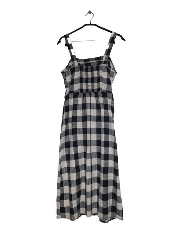Sukienka na naramkach w czarno-białą kratkę. Ozdobne guziki (dodatkowy guzik przy metce). Zapinana na pasek w pasie. Ściągacz na plecach.
