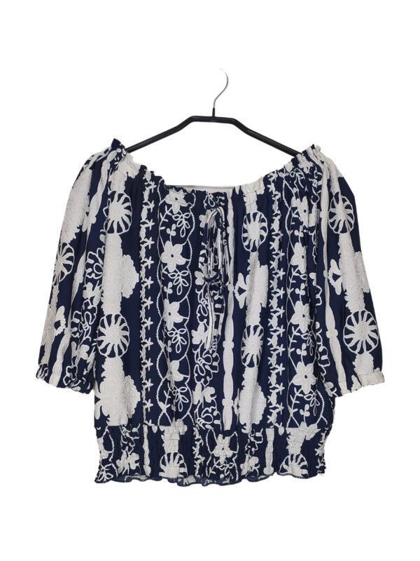 Granatowa bluzka typu hiszpanka z białymi koronkowymi elementami. Zwężna w pasie. U góry ozdobne wiązanie.