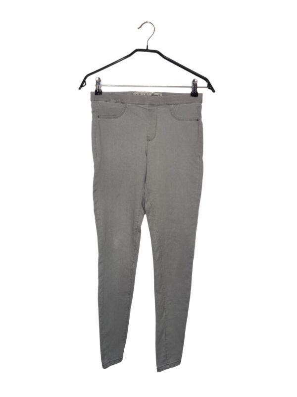 Szare rozciągliwe spodnie. Imitacja kieszeni z przodu. Widoczne lekkie ślady noszenia.