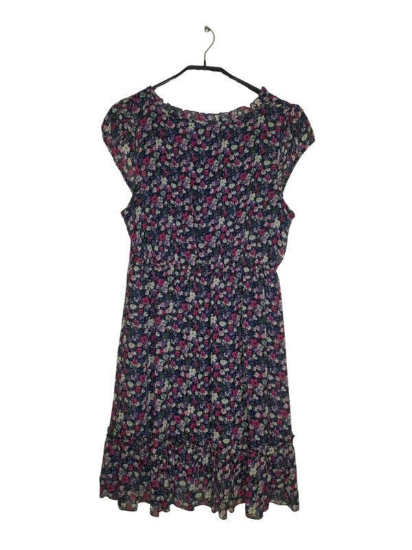 Fioletowa sukienka w białe 8 różowe kwiaty. Ściągana w pasie. Falbana na dole i przy szyi. Wiązana przy dekolcie.