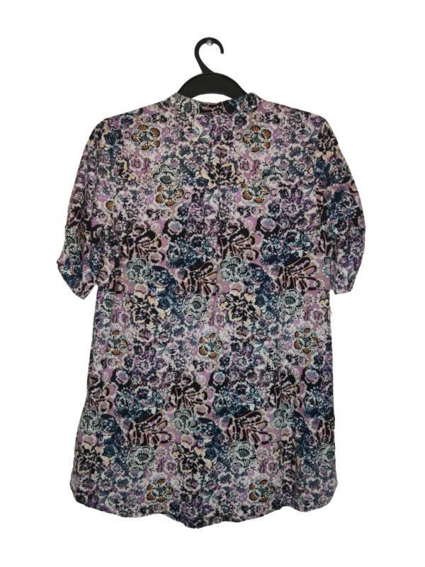 Koszula w różowe i białe kwiaty. Zapinana na 3 guziki przy dekolcie. Przy metce zapasowy guzik.