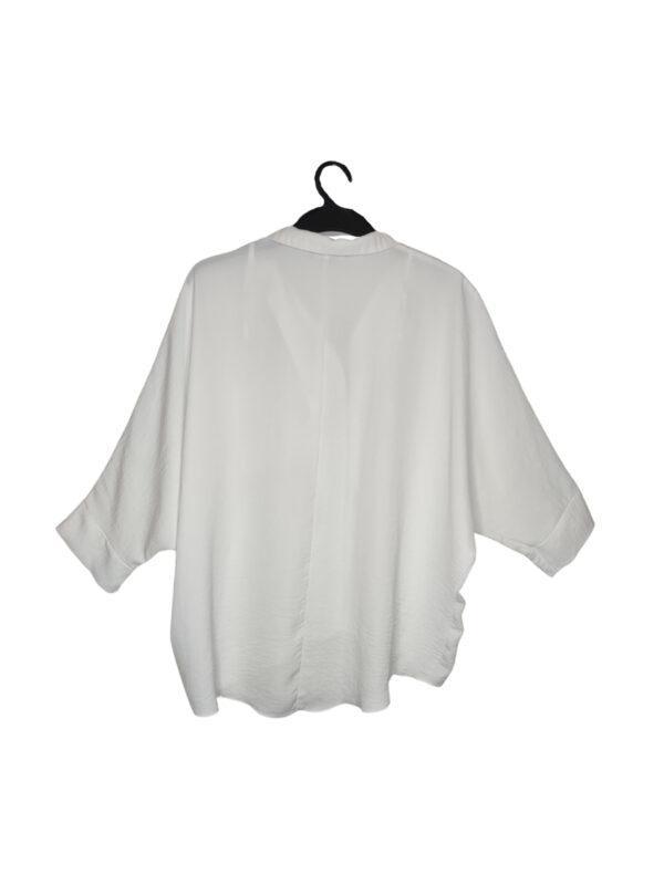 Biała koszula zapinana na guziki. Duża kieszeń po lewej stronie. Oversize.