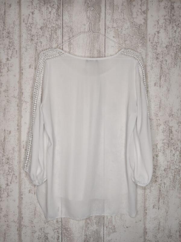 Biała koszula z koronkowymi wstawkami na rękawach.