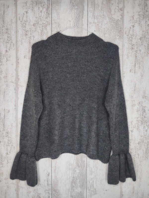 Szary sweter z półgolfem i bufiastymi rękawami.