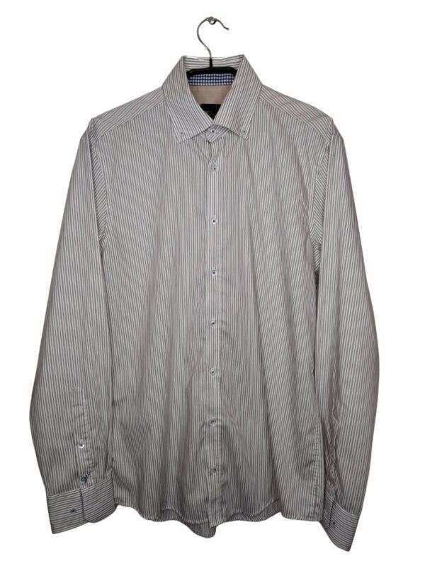 Biała koszula w kremowe i granatowe paski. Na dole przyszyte zapasowe guziki.