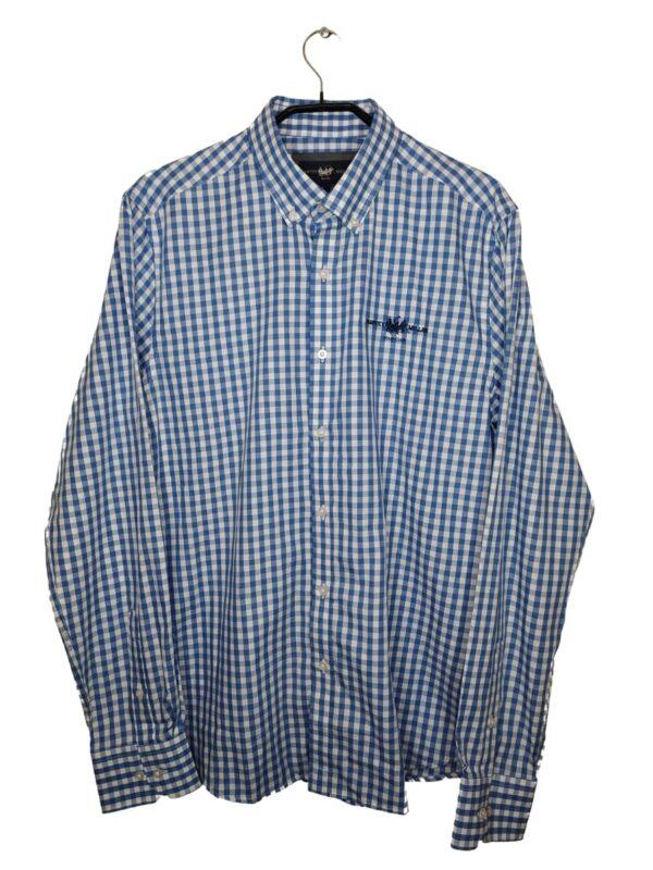 Koszula w biało-niebieską kratę. Po lewej stronie wyszyte logo. Przy metce są zapasowe guziki.