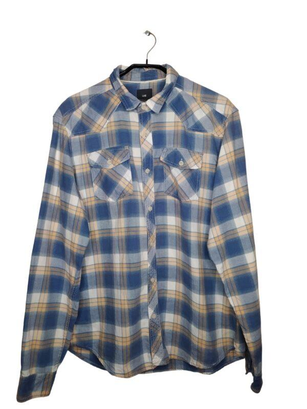 Biała koszula w niebieską i jasno pomarańczową kratkę. Z przodu kieszenie zapinane na guzik. Przy metce są zapasowe guziki.