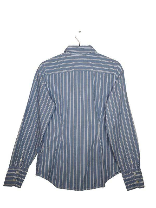 Niebieska koszula w podwójne białe paski. Po lewej stronie kieszonką z wyszytym logo. Przy metce jest zapasowy guzik.