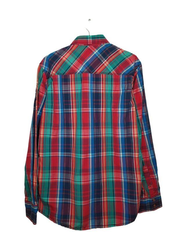 Koszula w kolorową kratkę. Nad kieszenią po lewej stronie znajduje się naszyty napis. Na lewym ramieniu ozdobna naszywka.