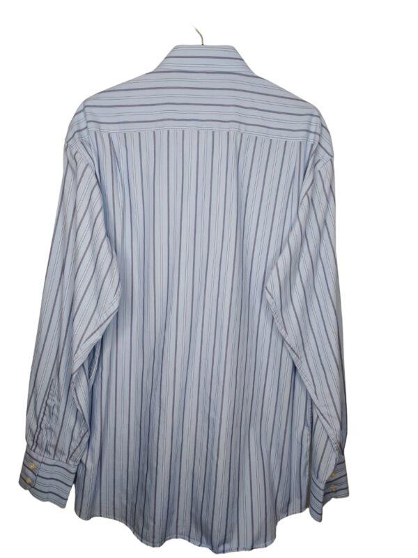 Błękitna koszula w paski w stonowanych kolorach. Na dole od spodu przyszyte zapasowe guziki.