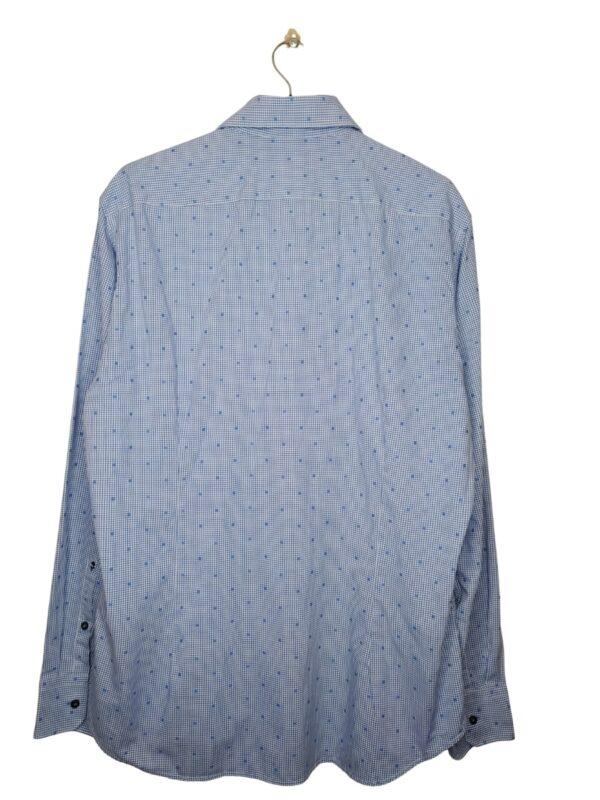 Biała koszula z delikatną niebieską kratką. Wzorek w kwadraty. Na dole od spodu przyszyte zapasowe guziki.
