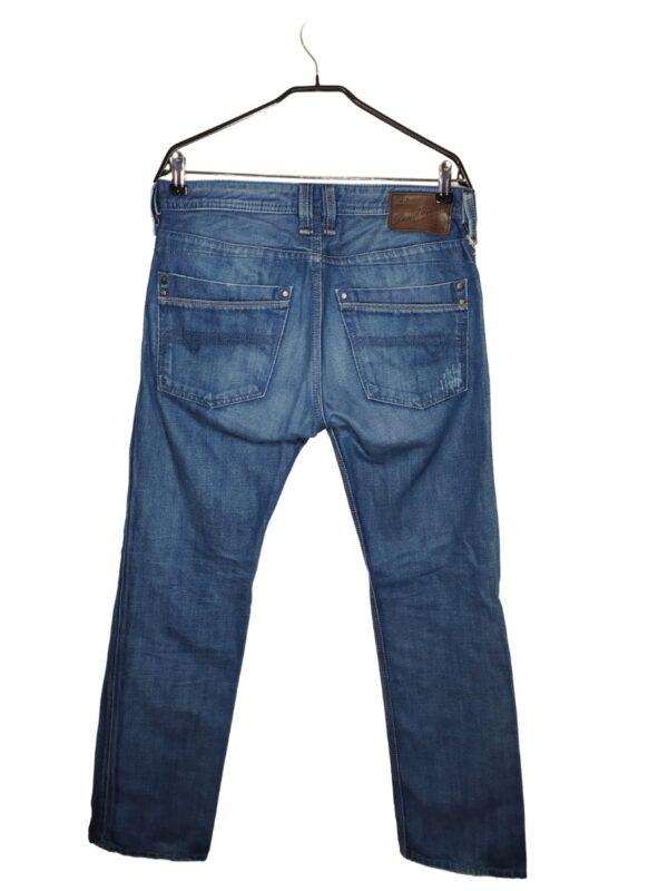 Spodnie jeansowe z ozdobnymi przetarciami. Zapinane na guziki zamiast rozporka. Widoczne lekkie ślady noszenia.