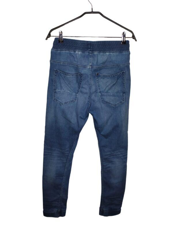 Jeansowe spodnie ze ściągaczem w pasie. Posiadają sznurek, nie ma rozporka.
