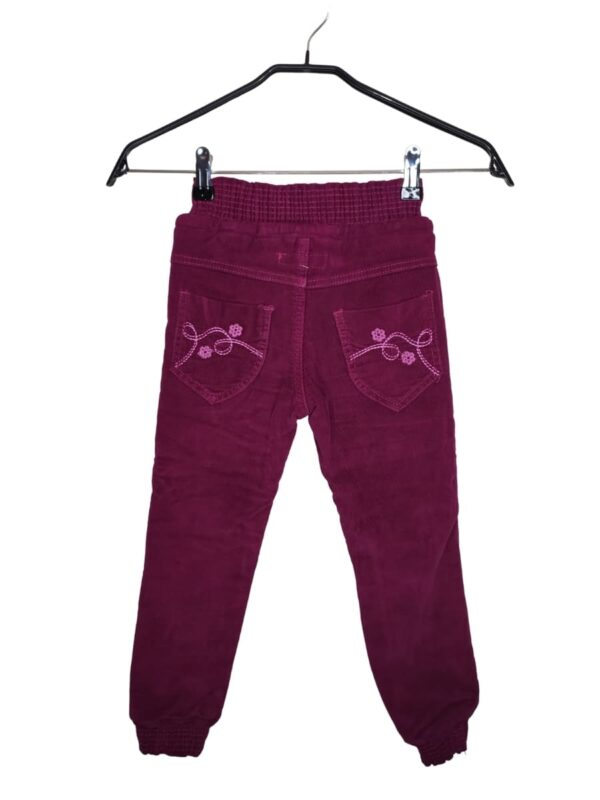 Bordowe spodnie sztruksowe że ściągaczem i sznurkiem w pasie. Przy kieszeniach z przodu i z tyłu ozdobne obszycia. Ściągacz przy nogawkach.
