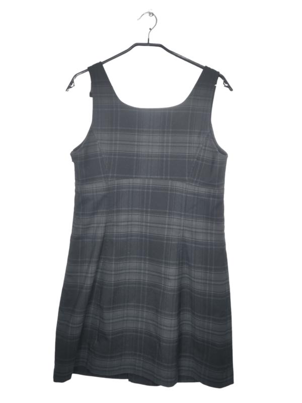 Szaro-czarna sukienka w kratkę z czterema ozdobnymi guzikami na przodzie. Jest lekko zmechacona, ma wychodzące nici przy guzikach.