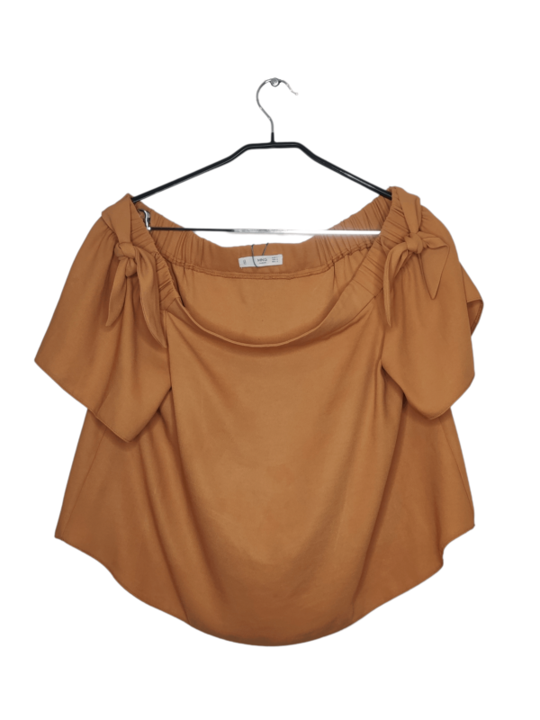 Pomarańczowa bluzka z odkrytymi ramionami. Na ramionach znajdują się ozdobne kokardki.