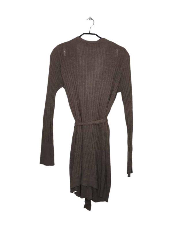 Długi sweter zapinany na guziki z kieszeniami z przodu. W zestawie pasek do przewiązania w pasie.